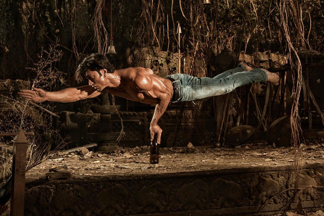 Vidyut Jamwal Top Model India - He is performing action in the picture, balancing his body on a single bottle