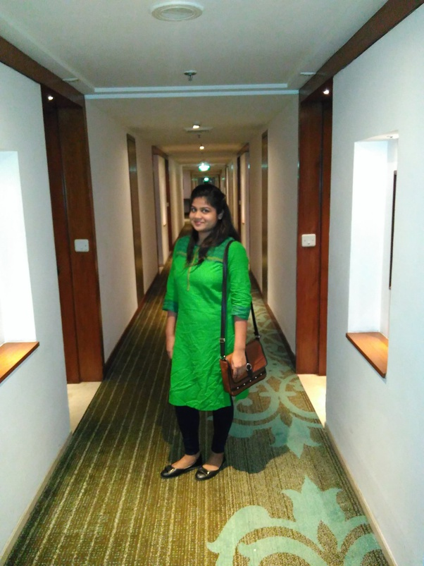 before photo weight loss transformation garima verma - posing in green suit in hotel's lobby