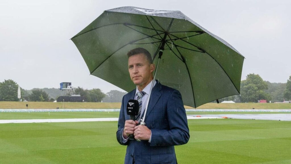 Craig Cumming standing with Umbrella during commentary