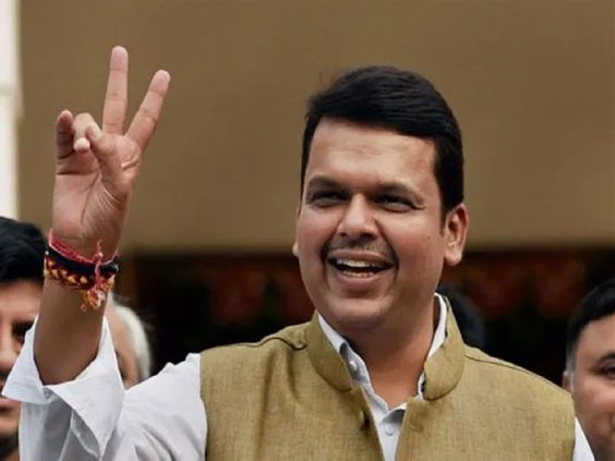 Devendra Fadnavis wearing nehru suit showing victory sign with smile