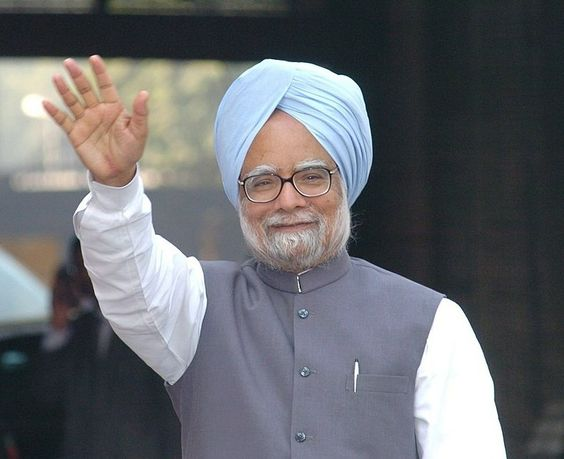 Manmohan Singh in Blue turbon  and nehru suit smiling and raising hand