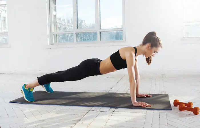 Push Up - woman in her black sportswear doing on her yoga mat