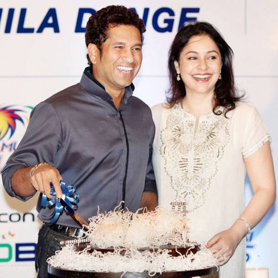 Sachin Tendulkar Weds November Born Anjali - both are laughing in the picture. Anjali is in Indian attires and Sachin is wearing formal grey shirt cutting cake