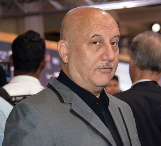 Anupam Kher wearing grey coat with black shirt in standing pose