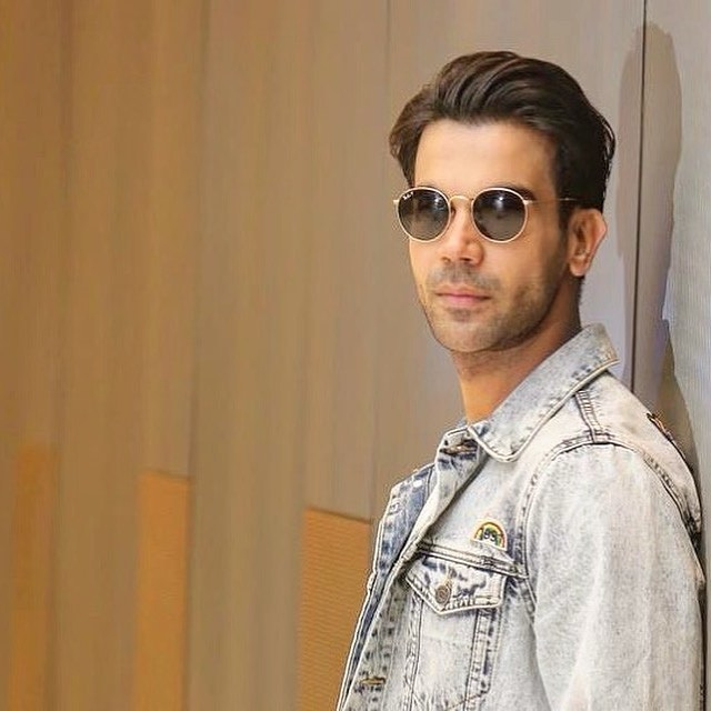 Rajkummar Rao pose with cool slicked back look & standing in front of wall with sunglasses
