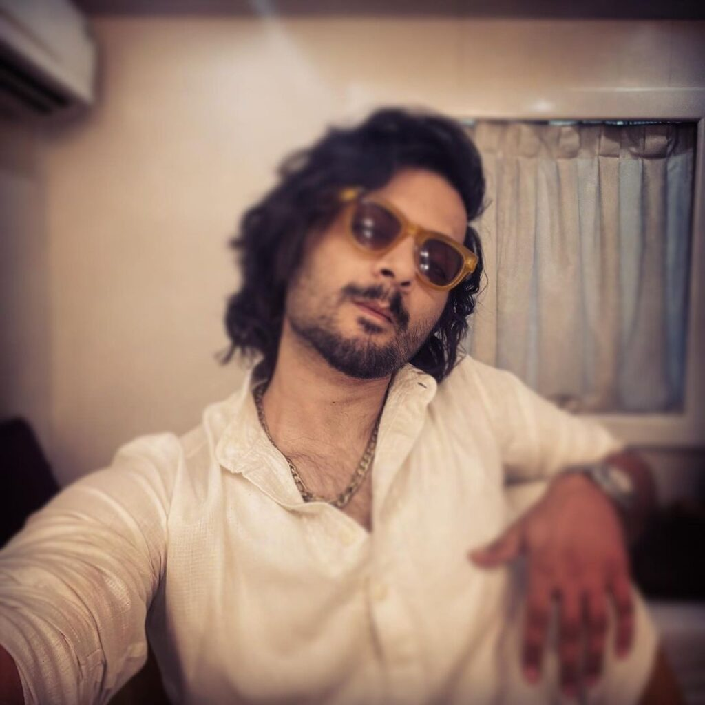 Ali Fazal pose with curly waves style wearing white shirt with shades