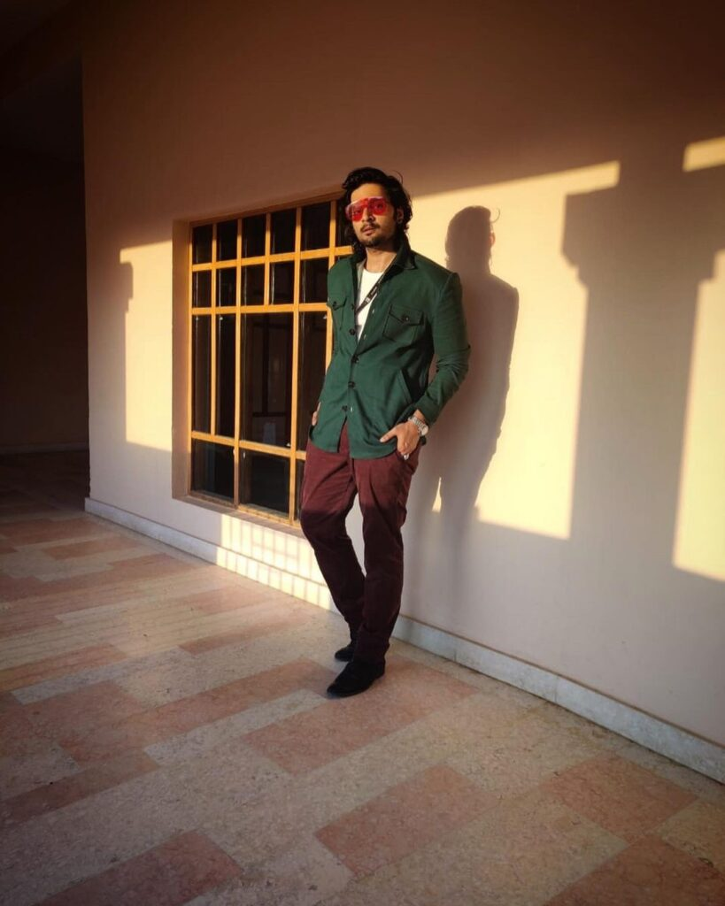 Ali Fazal pose with long classy hairstyle & standing in front of wall
