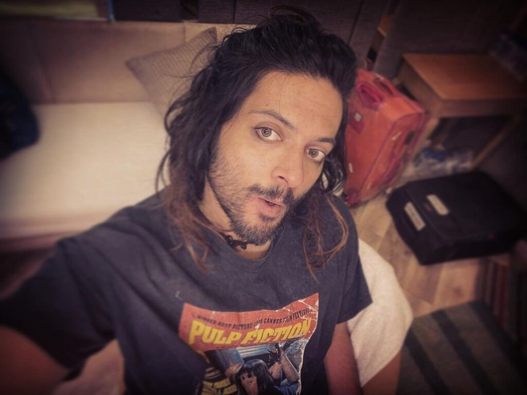 Ali Fazal pose with long hair with highlights hairstyle with black tshirt