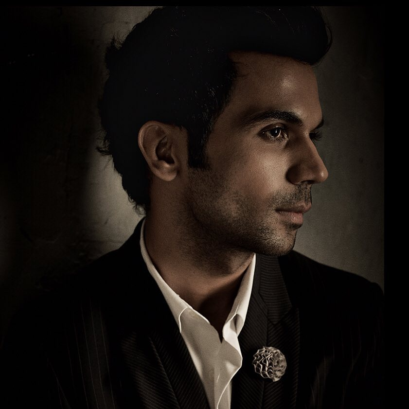 Rajkummar Rao pose with Sexy side-swept hairstyle & wear black coat with white shirt