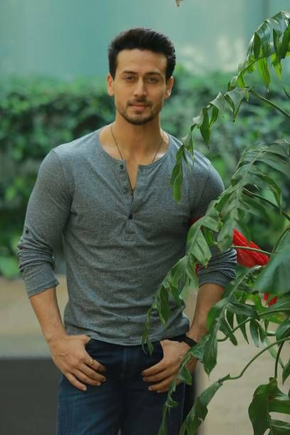 Tiger Shroff standing in garden and wearing grey tshirt & blue jeans