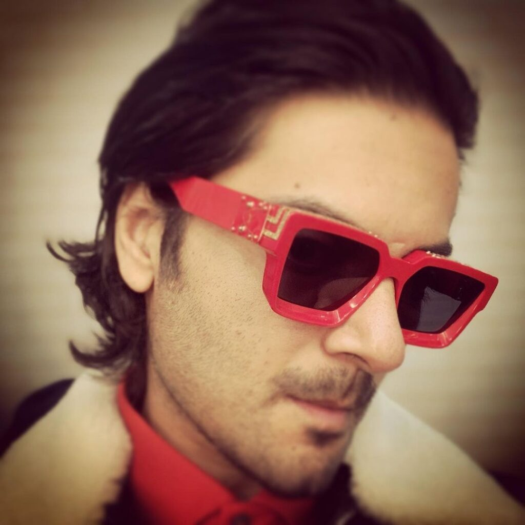 Ali Fazal pose with vintage slicked back hairstyle with dashing shades