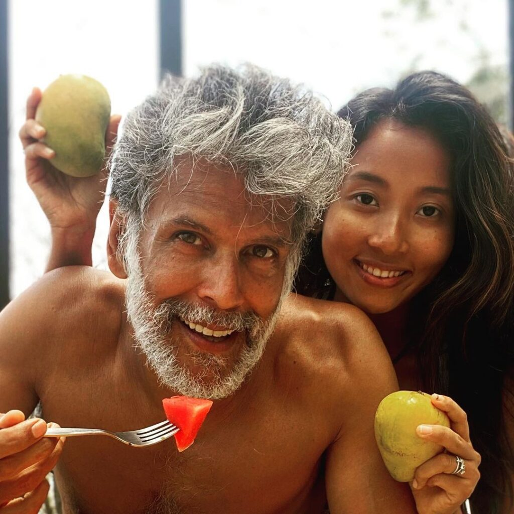 Milind Soman trending grey haircut with his wife