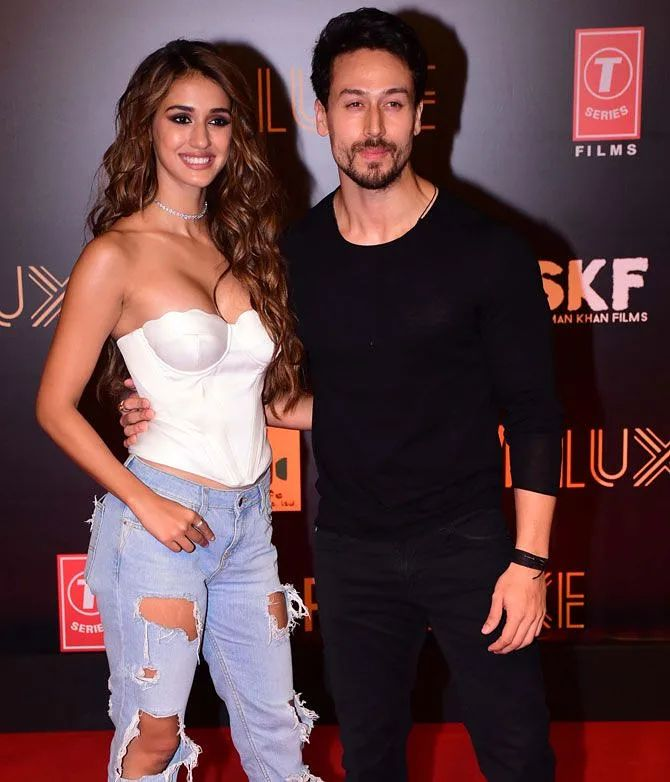 Tiger Shroff in black outfit and Disha Patani in white top smiling and posing - bollywood couples in real life